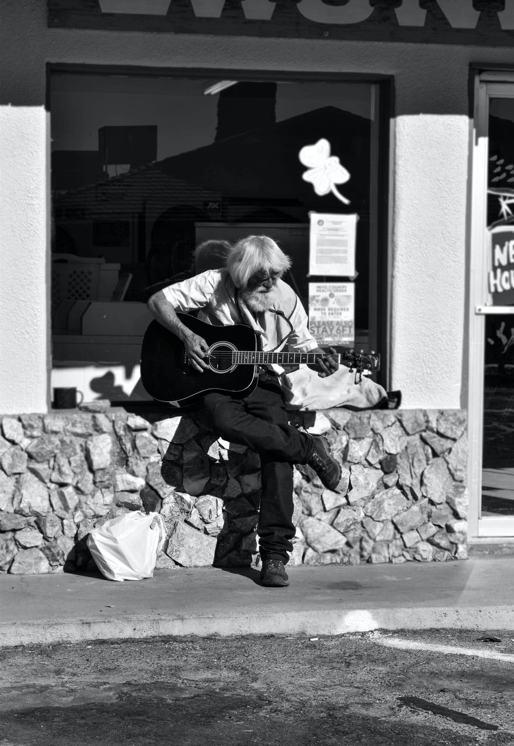 woman playing acoustic guitar in grayscale photography
