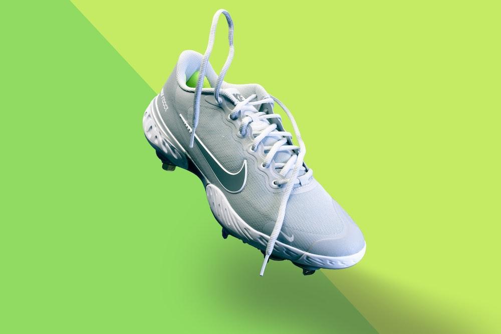 white nike athletic shoe on green textile