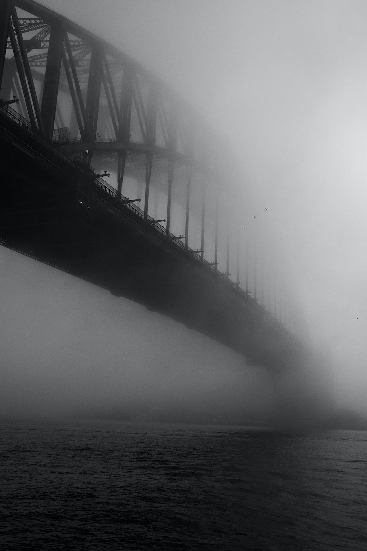 grayscale photo of bridge over sea