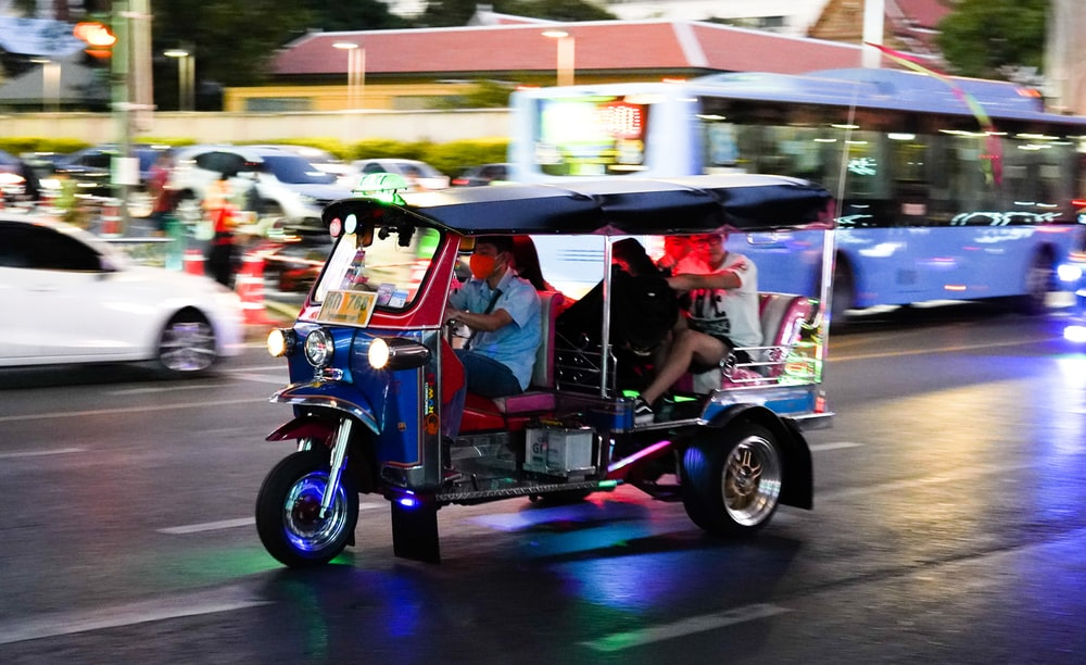 2 people riding on blue and white auto rickshaw