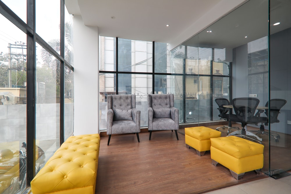 yellow sofa near glass window