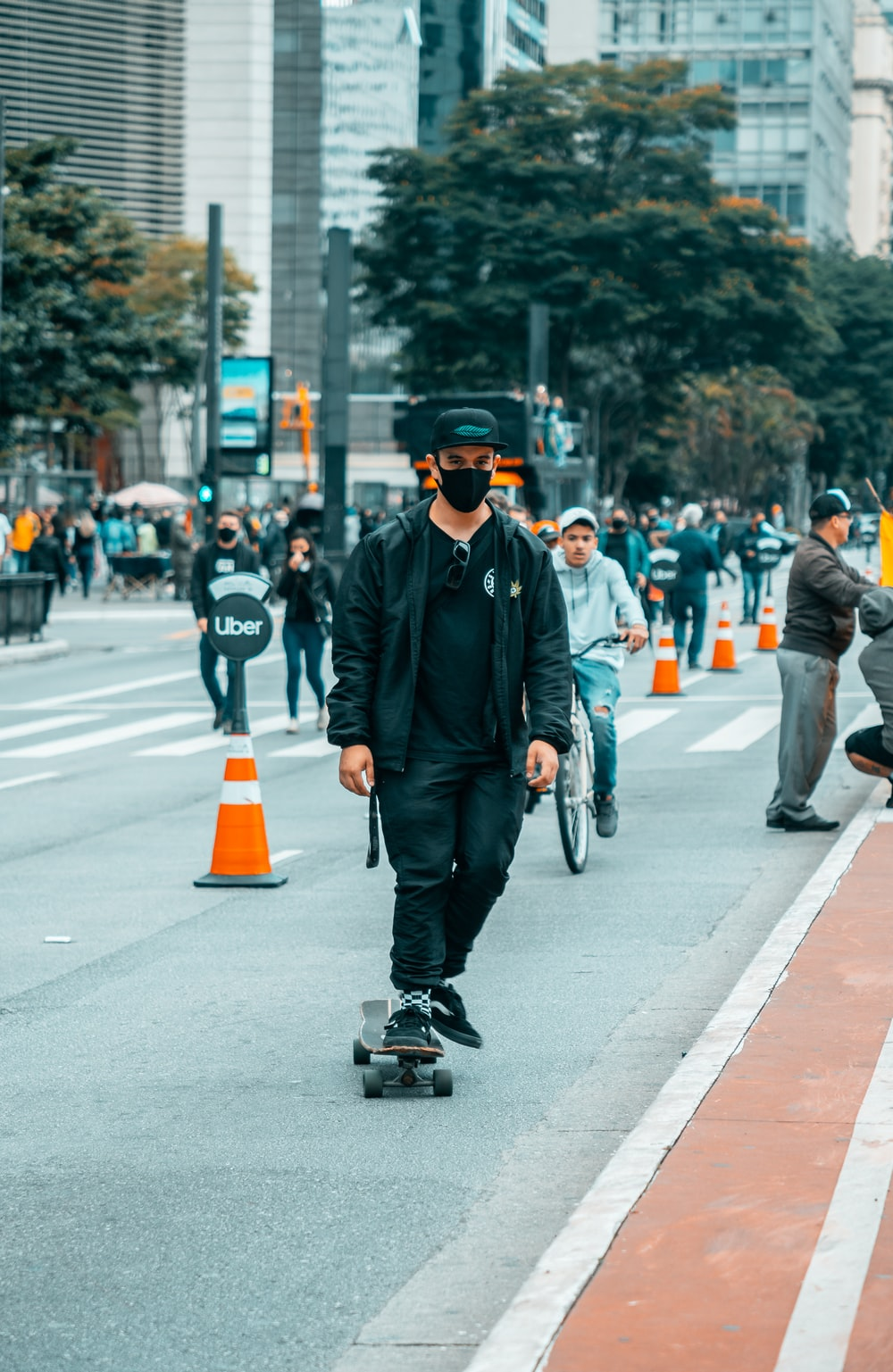 man in black jacket and black cap riding on black kick scooter on gray concrete road