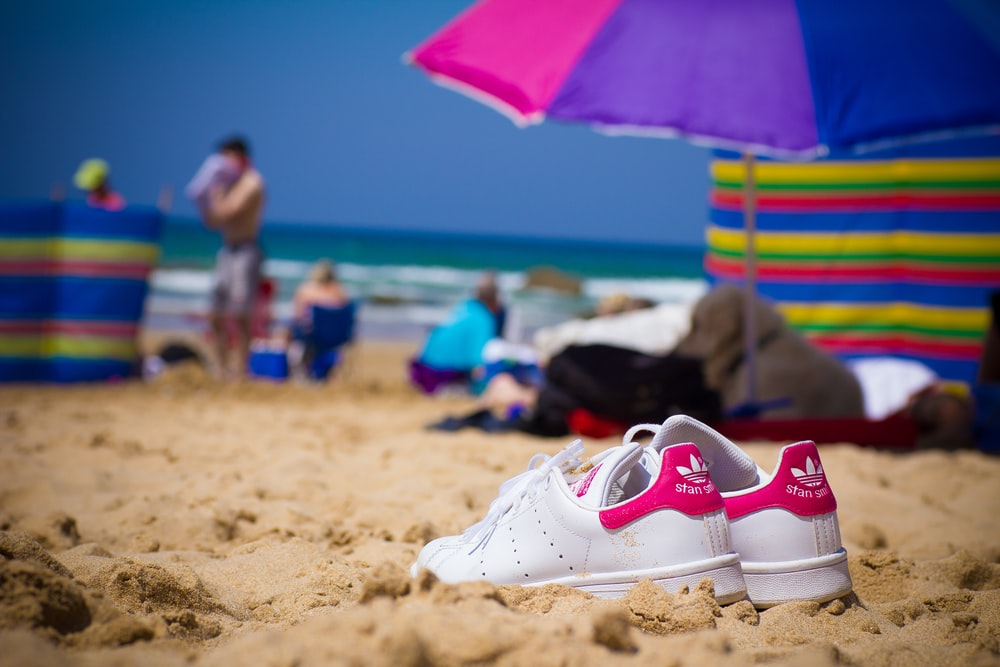 white and red nike sneakers on beach