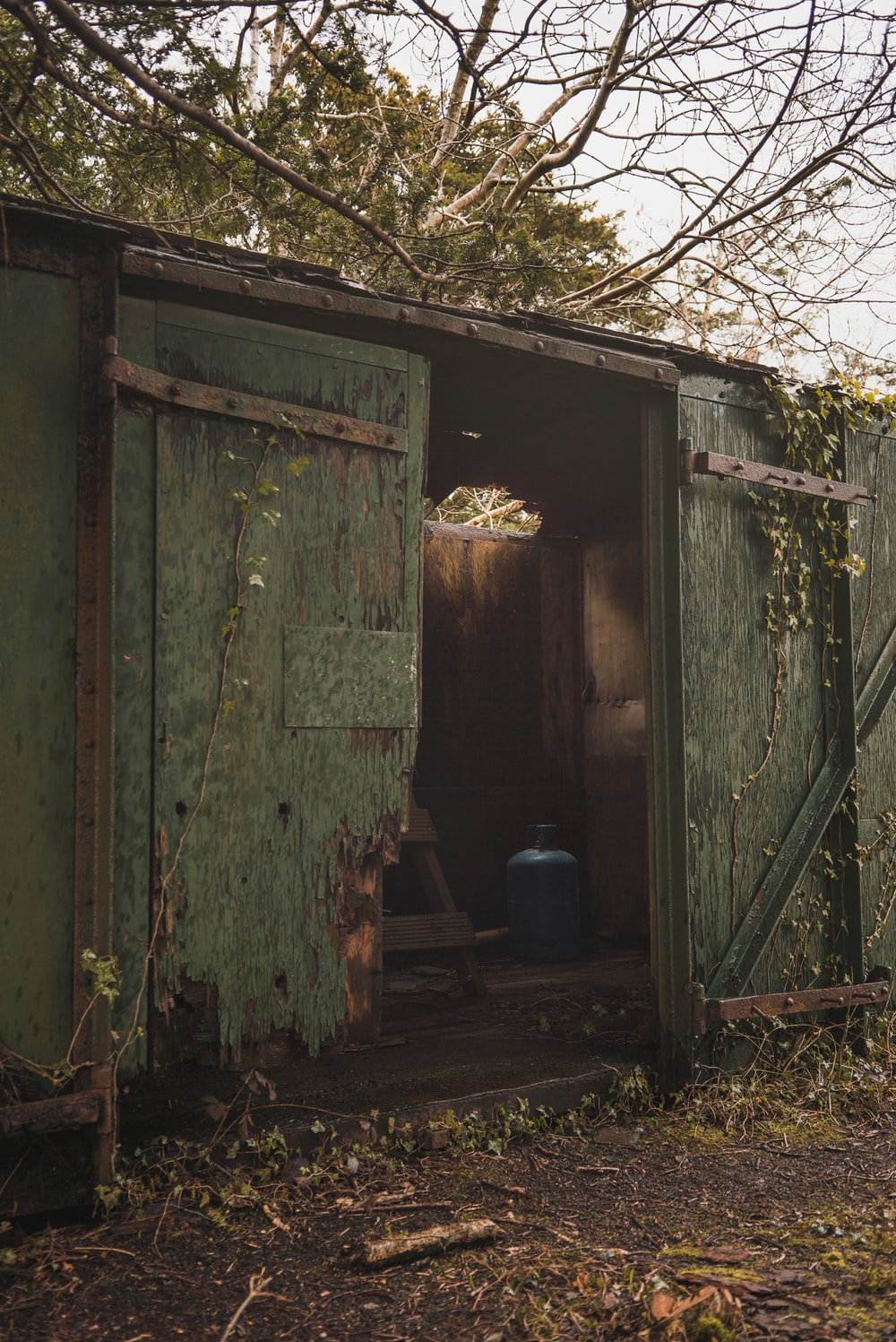 green wooden door near blue plastic container