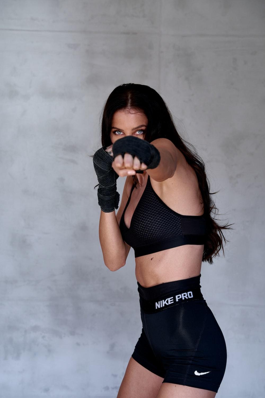woman in black sports bra and black leggings holding black heart shaped ornament
