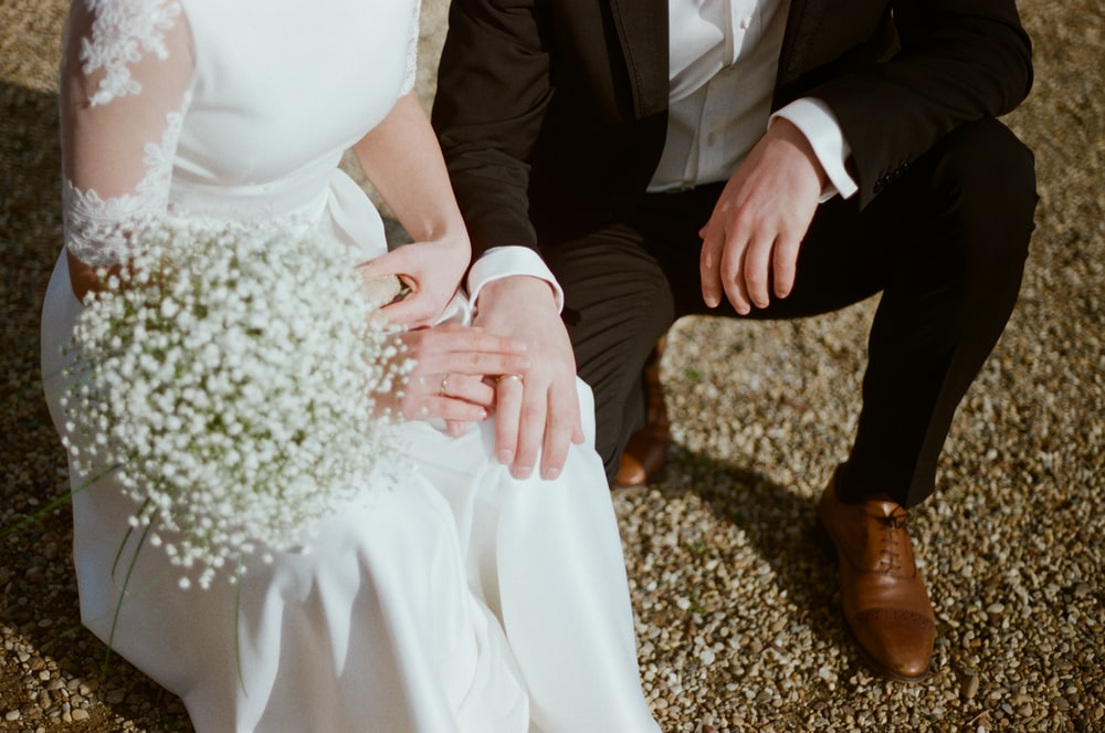 man in black suit jacket and woman in white dress