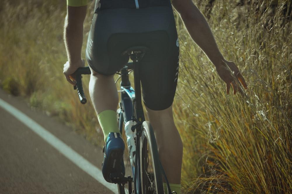 man in black shorts riding bicycle on road during daytime