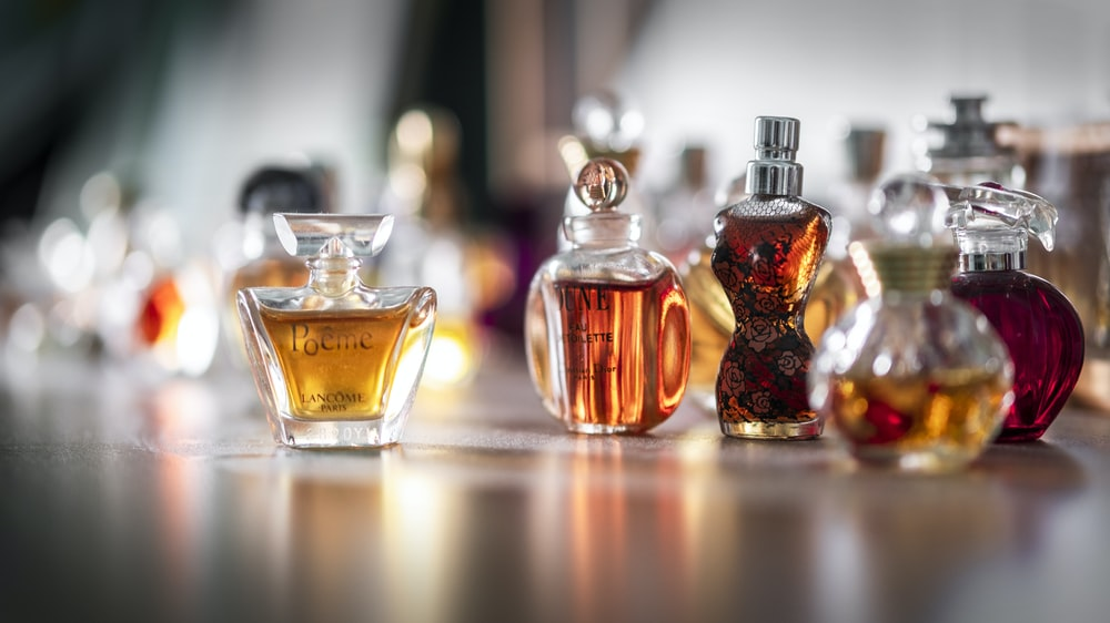 selective focus photography of clear glass perfume bottle
