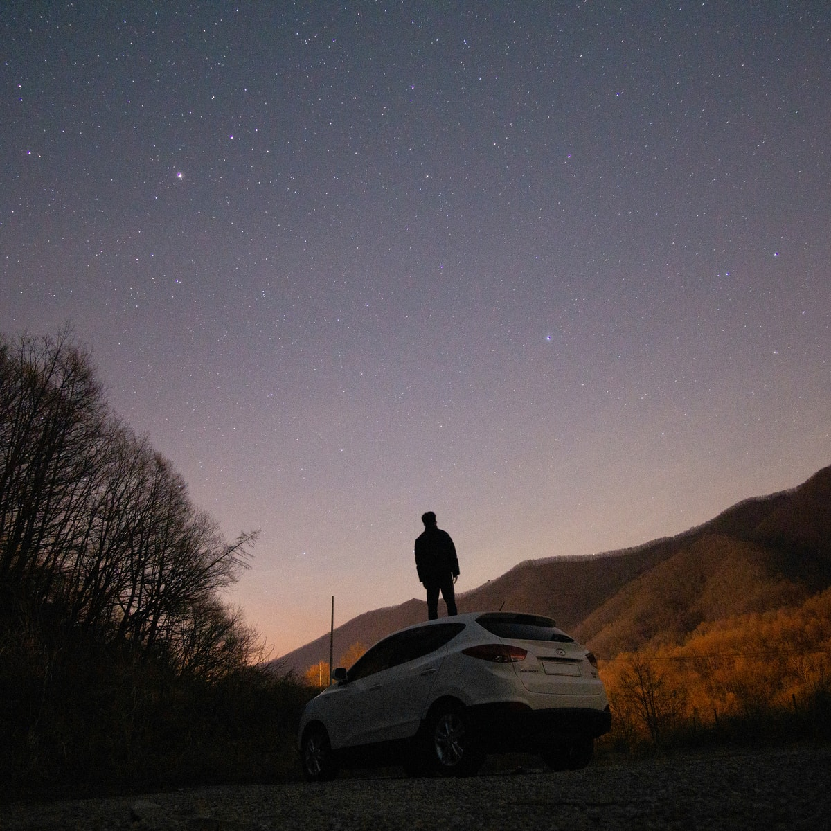 silhouette of man sitting on white car during night time