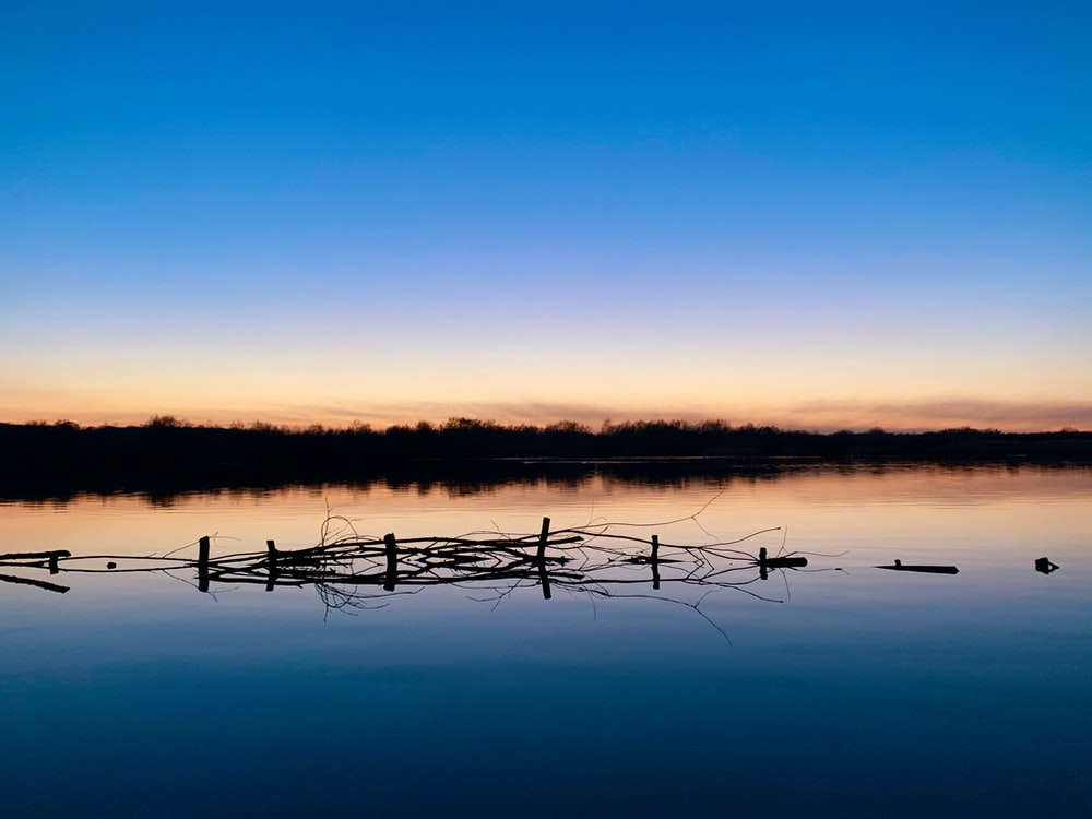 brown wooden fence on lake during sunset