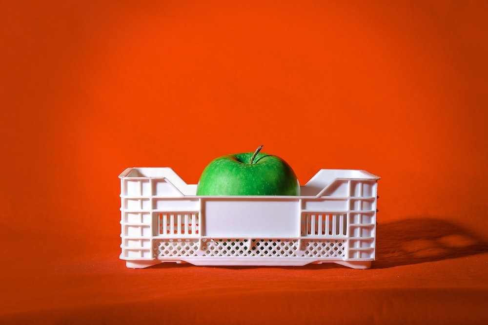 red apple on white plastic crate