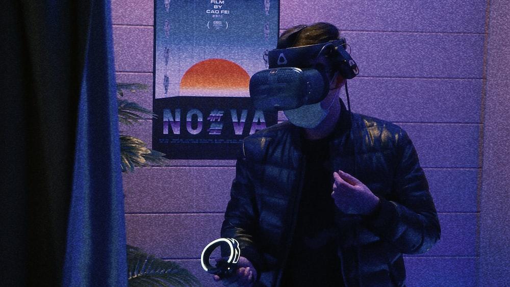 man in black leather jacket holding black and blue dslr camera