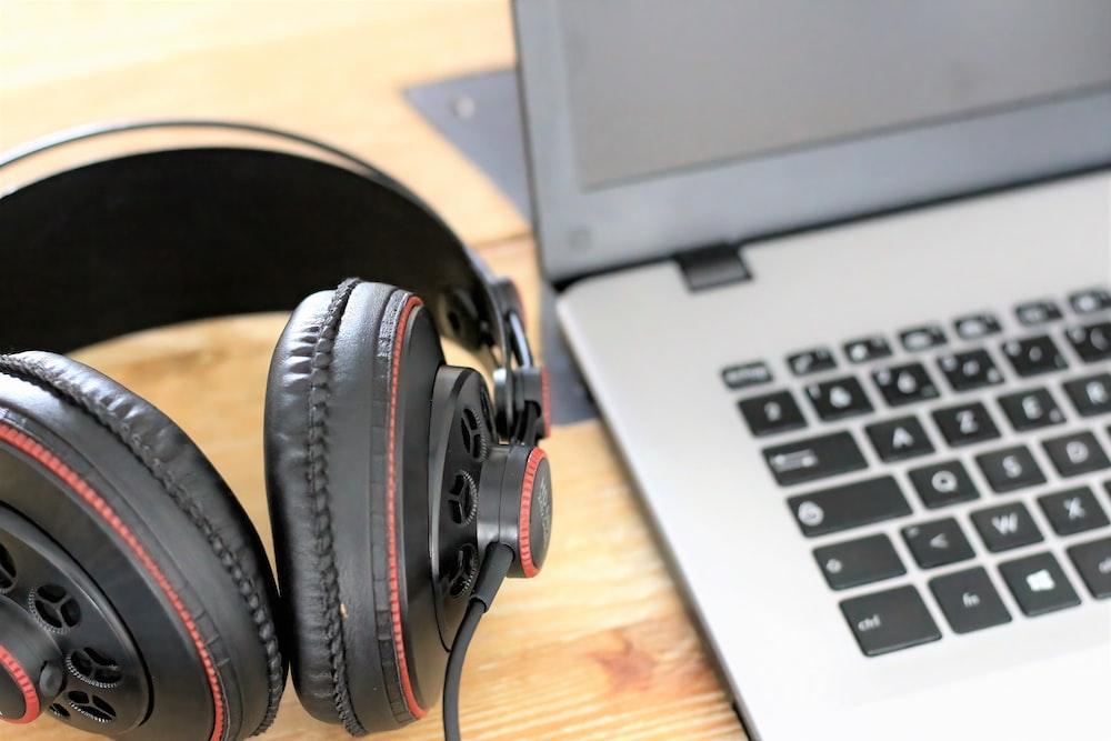 black and gray headphones on macbook pro