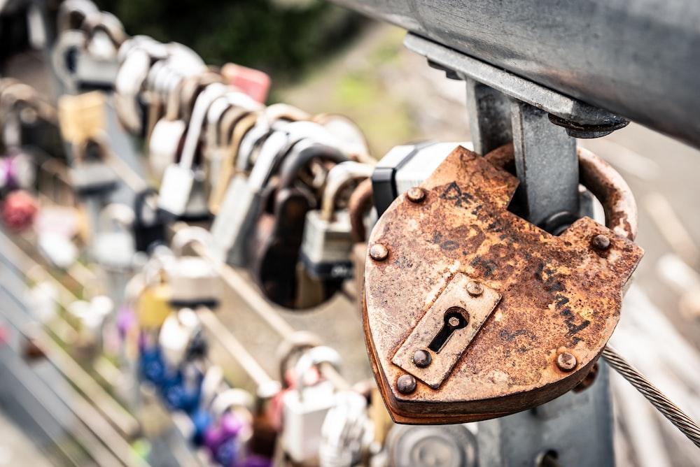 brown padlock on black metal fence during daytime