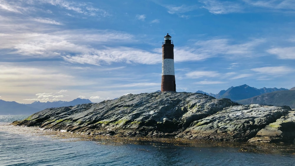 brown and black lighthouse on rocky hill near body of water under blue and white cloudy