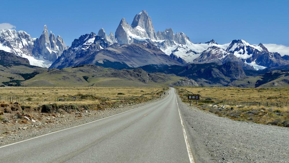 gray asphalt road near mountain range under blue sky during daytime