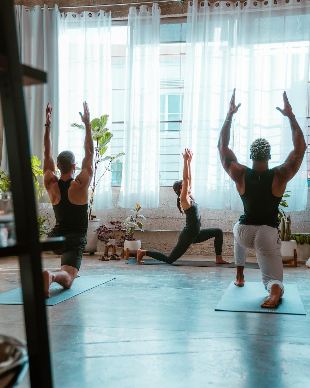 3 women doing yoga on blue yoga mat