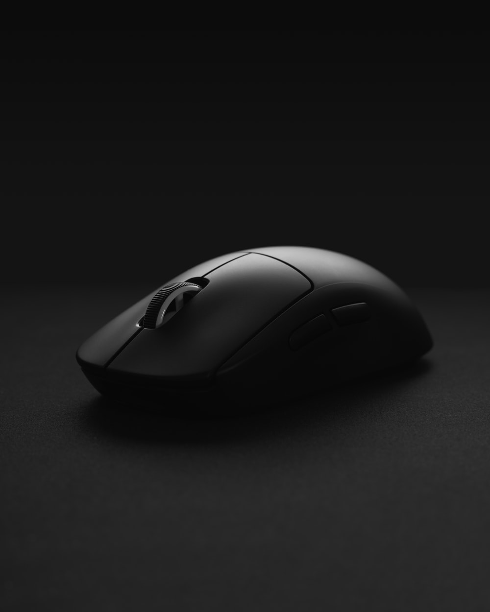 black cordless computer mouse on black surface