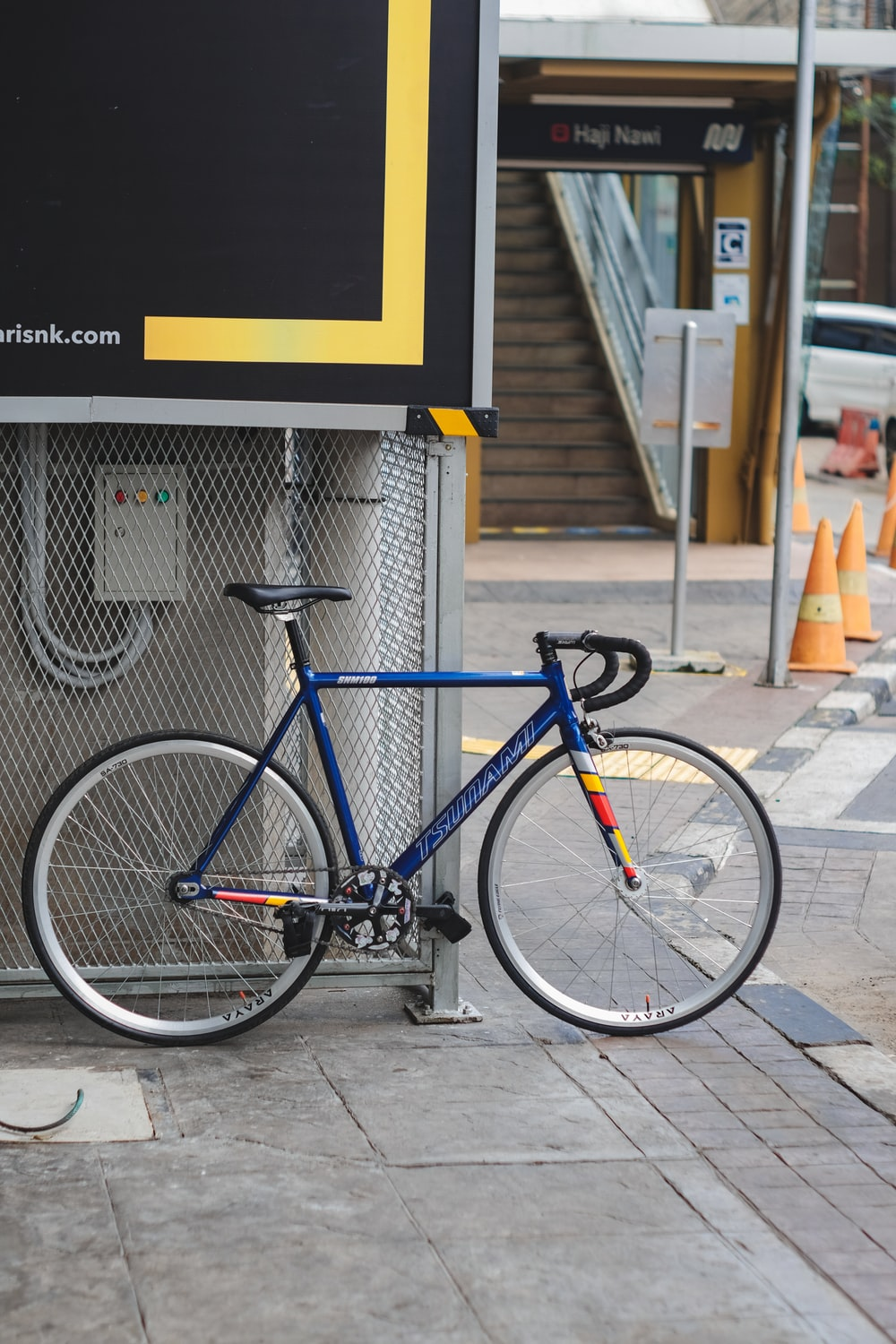 blue and black road bike parked beside white concrete building during daytime