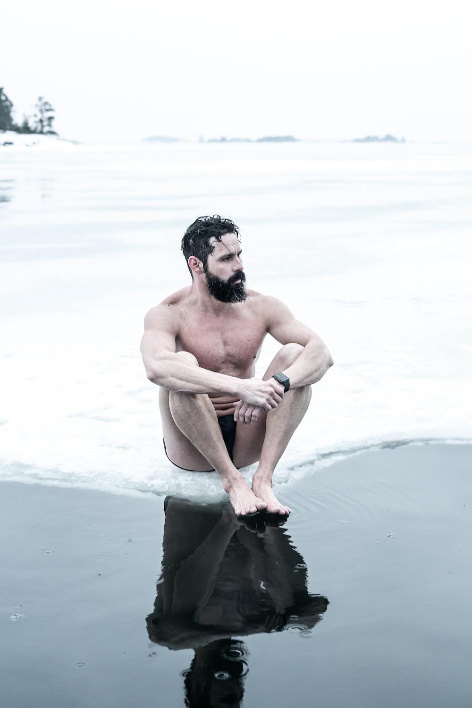 topless man sitting on rock on beach
