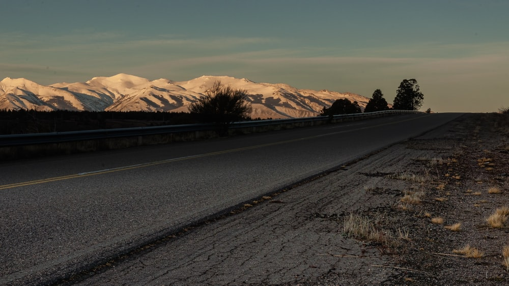 black asphalt road near brown mountains during daytime