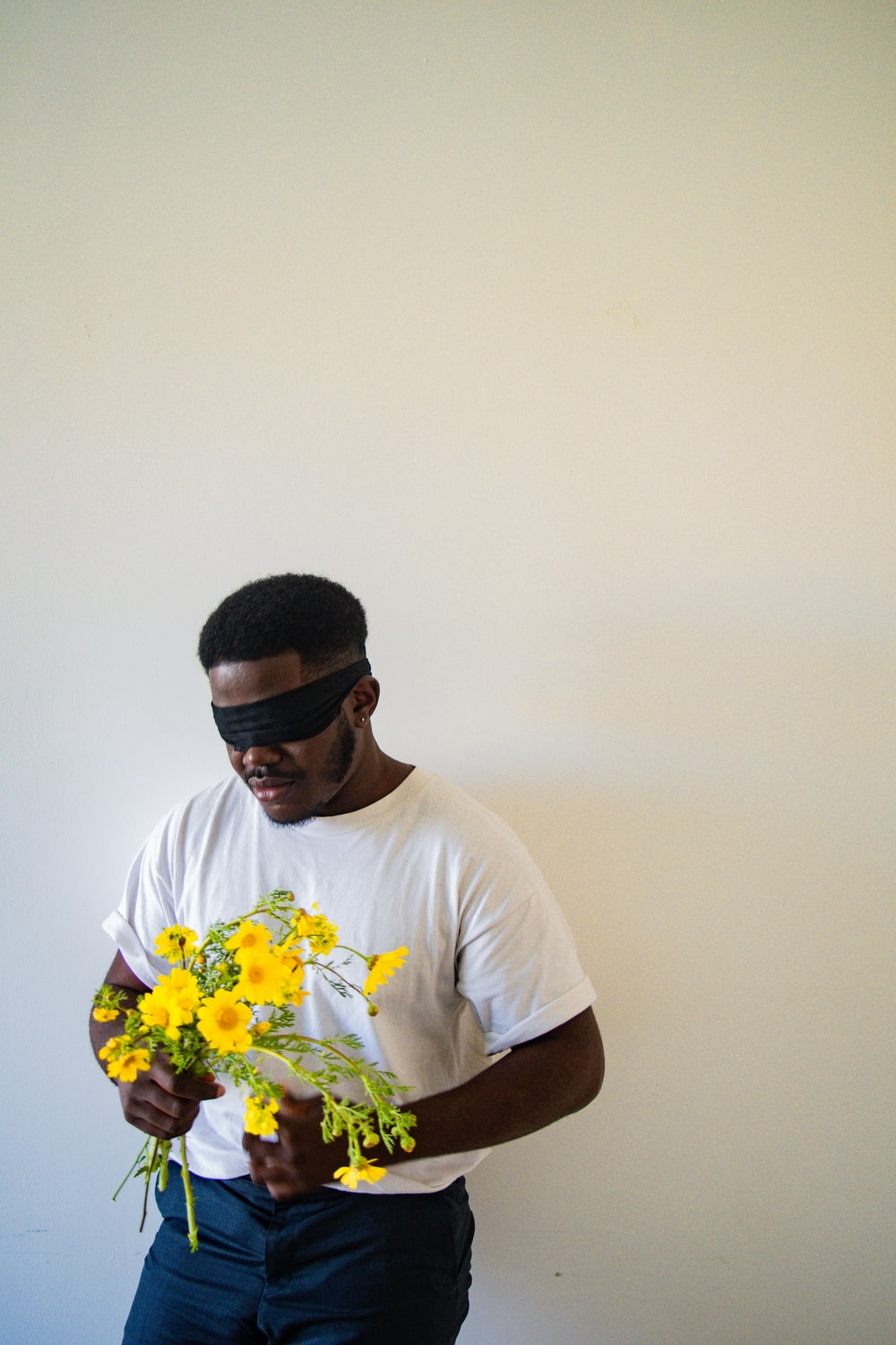 man in white crew neck t-shirt holding yellow flower bouquet