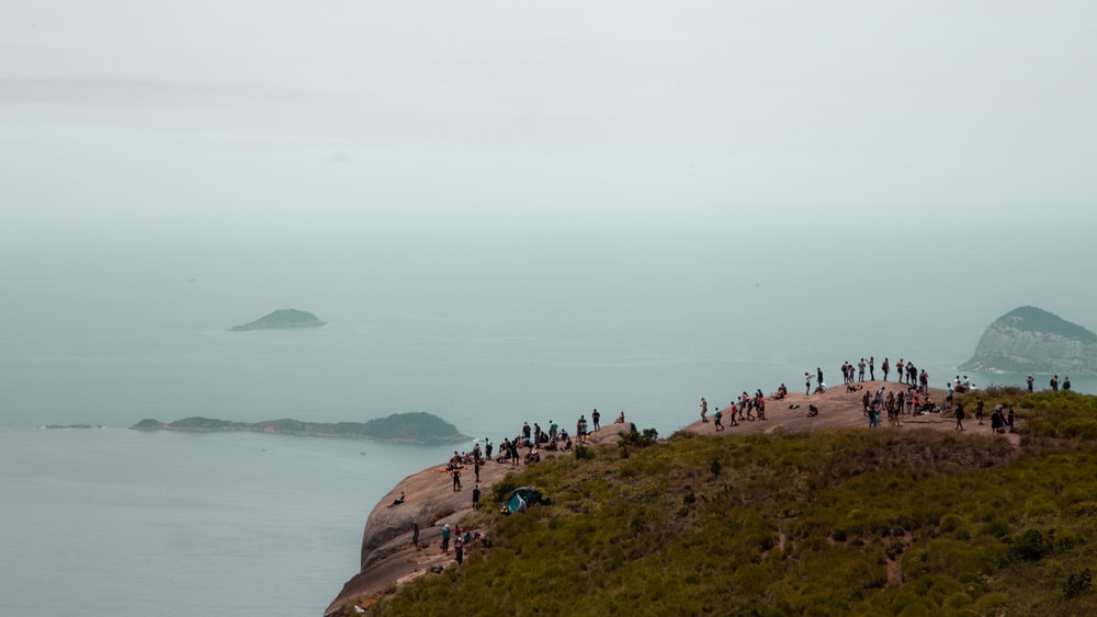 people on brown rock formation near body of water during daytime