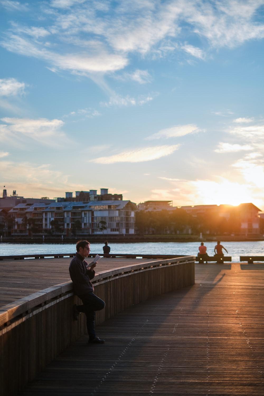 man in black jacket sitting on brown wooden dock during sunset