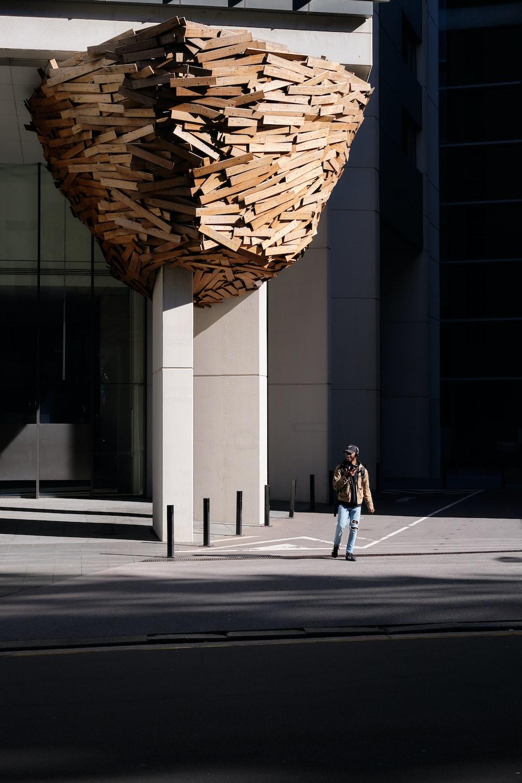 woman in black jacket and black pants walking on sidewalk during daytime