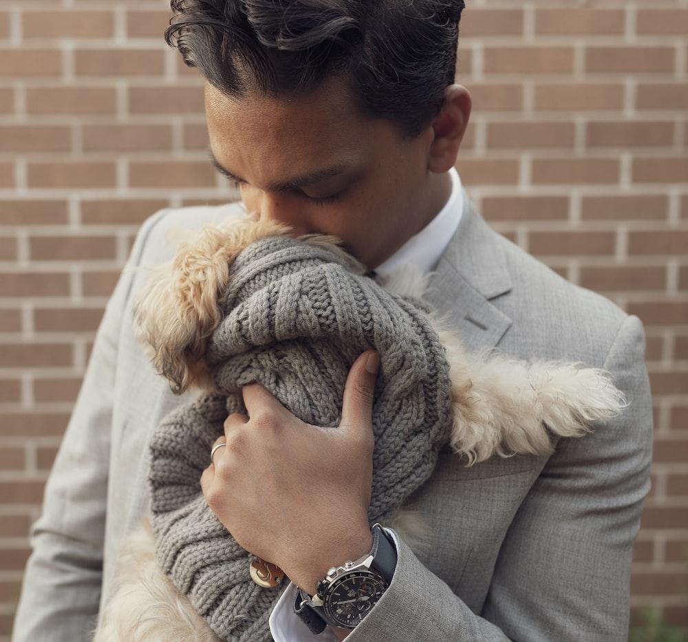 man in black suit jacket hugging woman in white fur coat