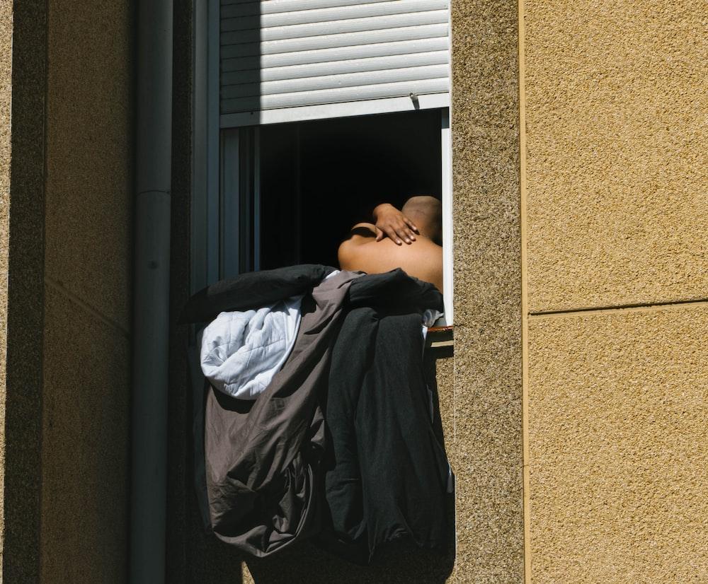 man in black t-shirt lying on black wooden door