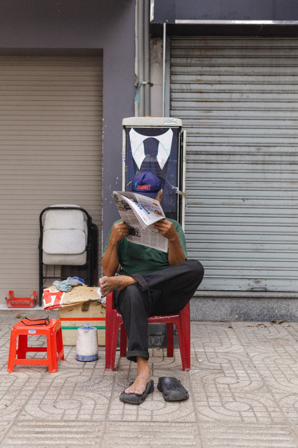 man in green t-shirt reading book sitting on red plastic chair
