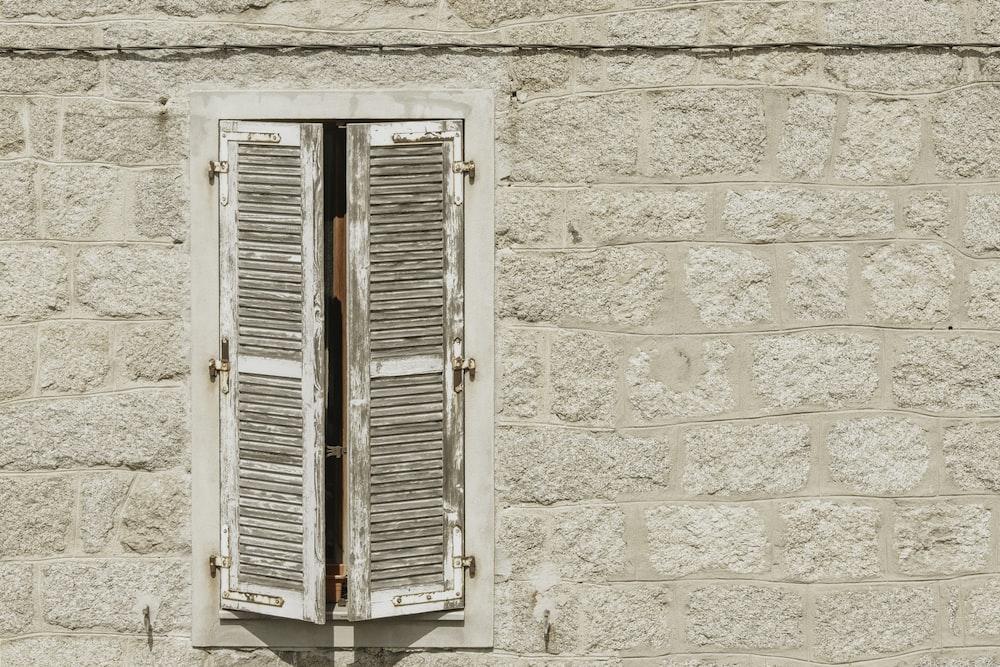 white wooden window on white concrete wall