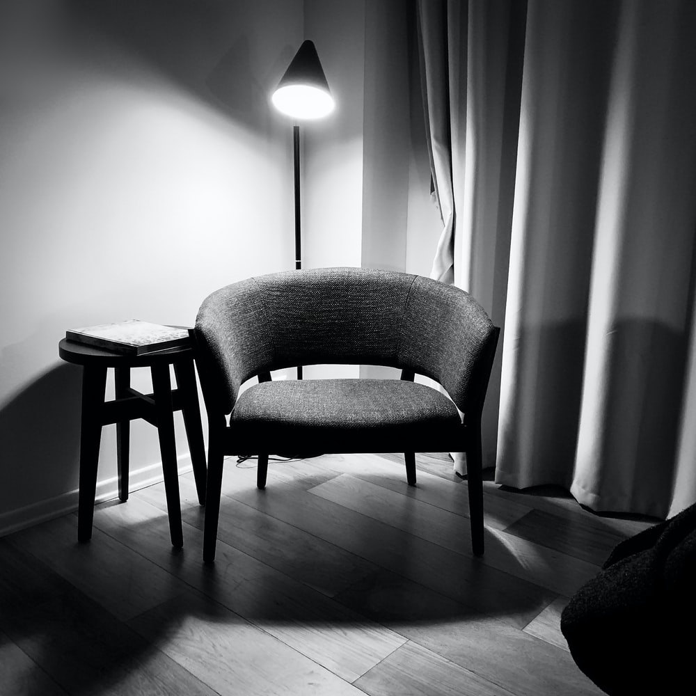 gray padded chair beside white wall