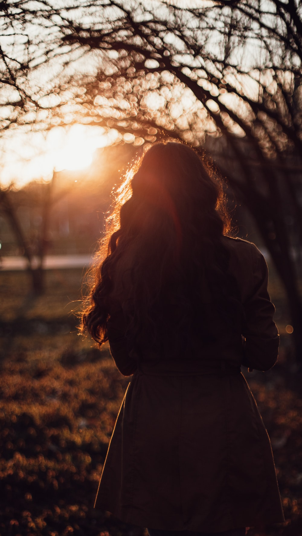 woman in black coat standing near trees during sunset