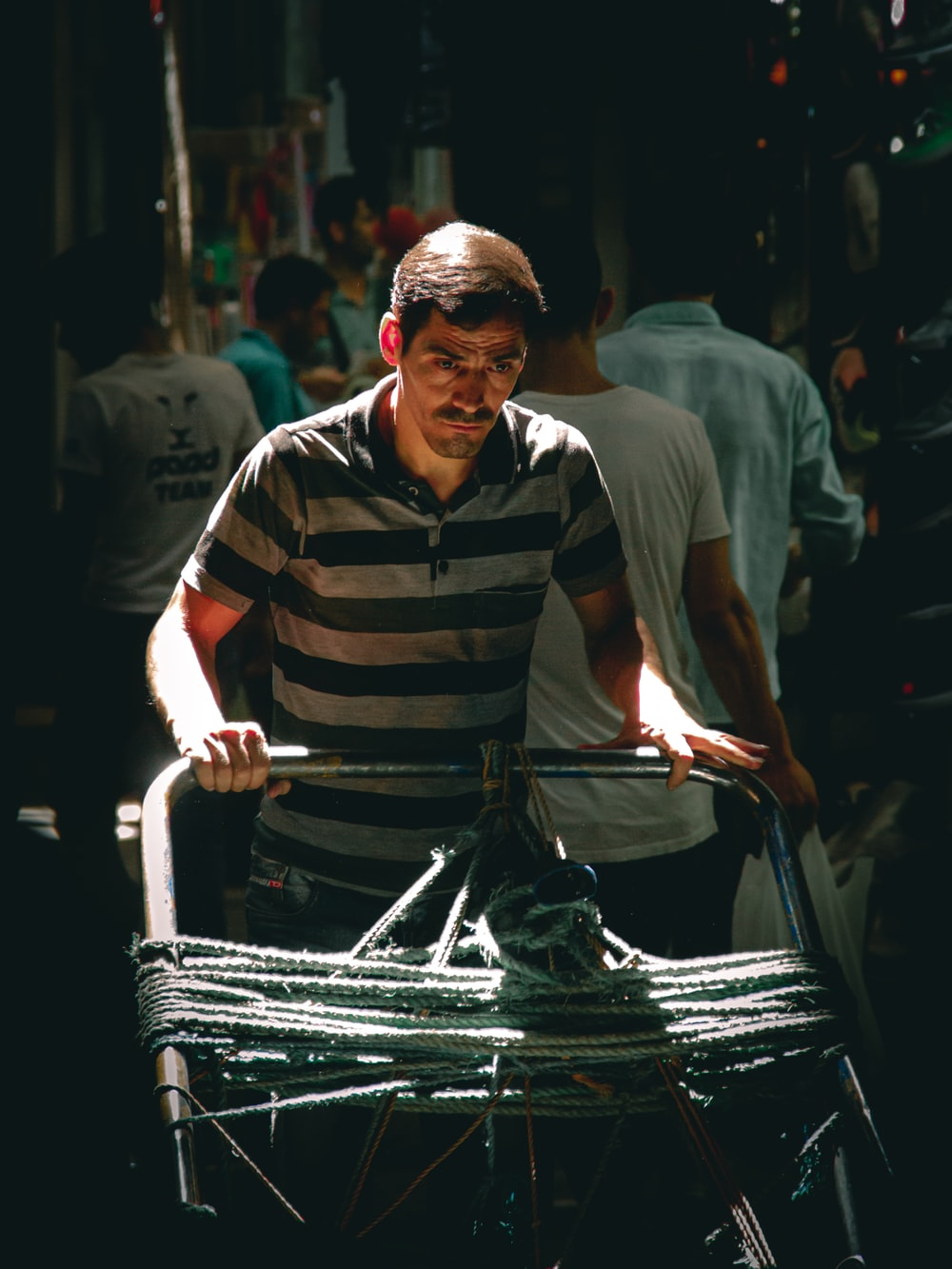 man in black and white stripe polo shirt holding black plastic bag
