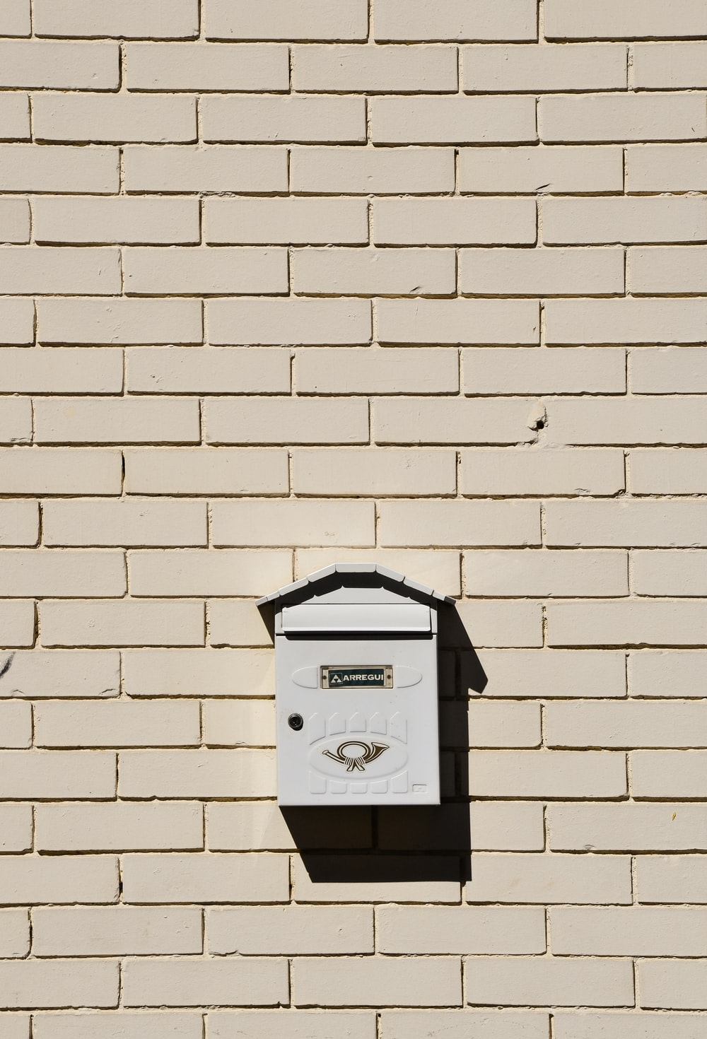 black mail box mounted on white brick wall