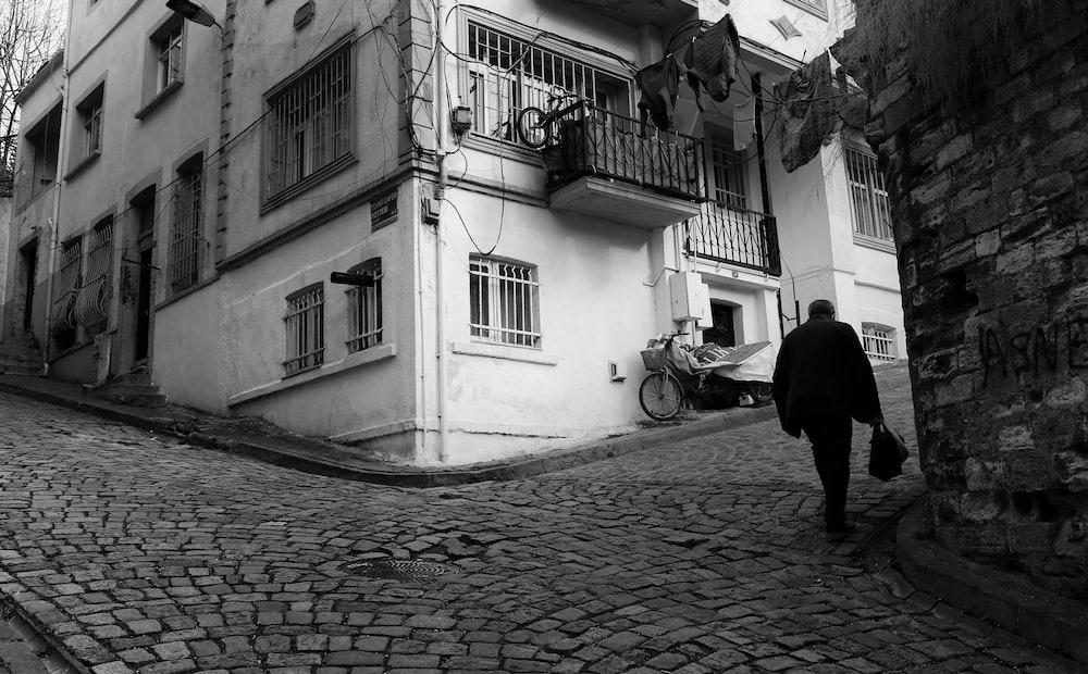 man in black jacket walking on sidewalk near building during daytime