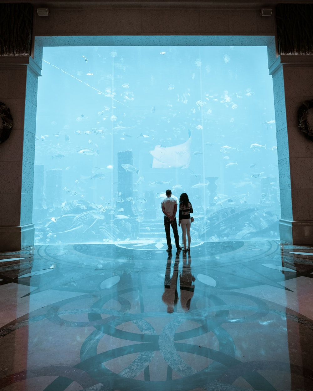 man and woman standing on blue and white floor tiles