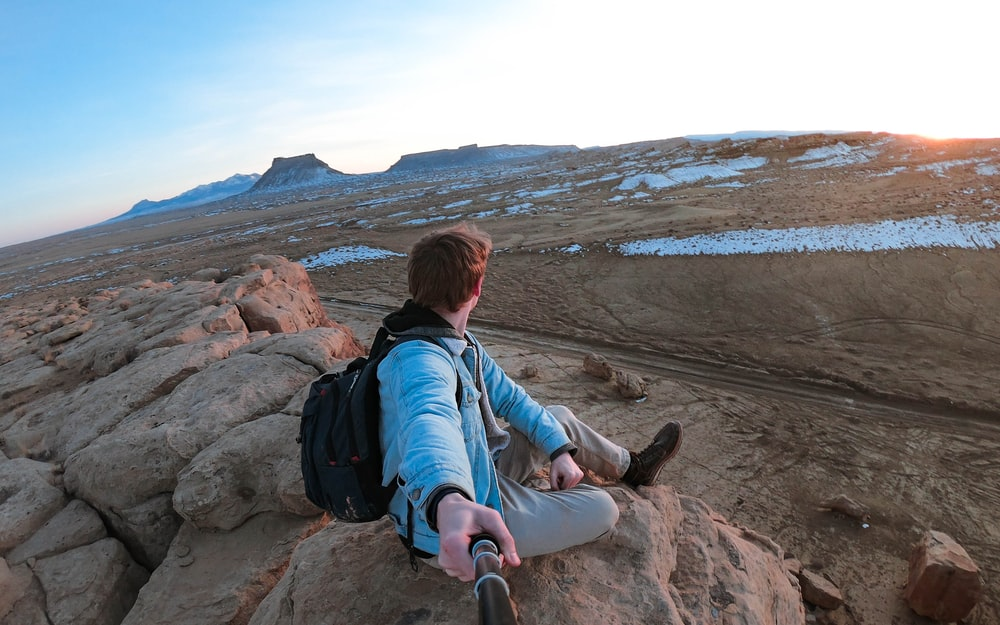 woman in blue jacket sitting on rock during daytime
