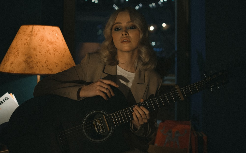 woman in black blazer playing acoustic guitar