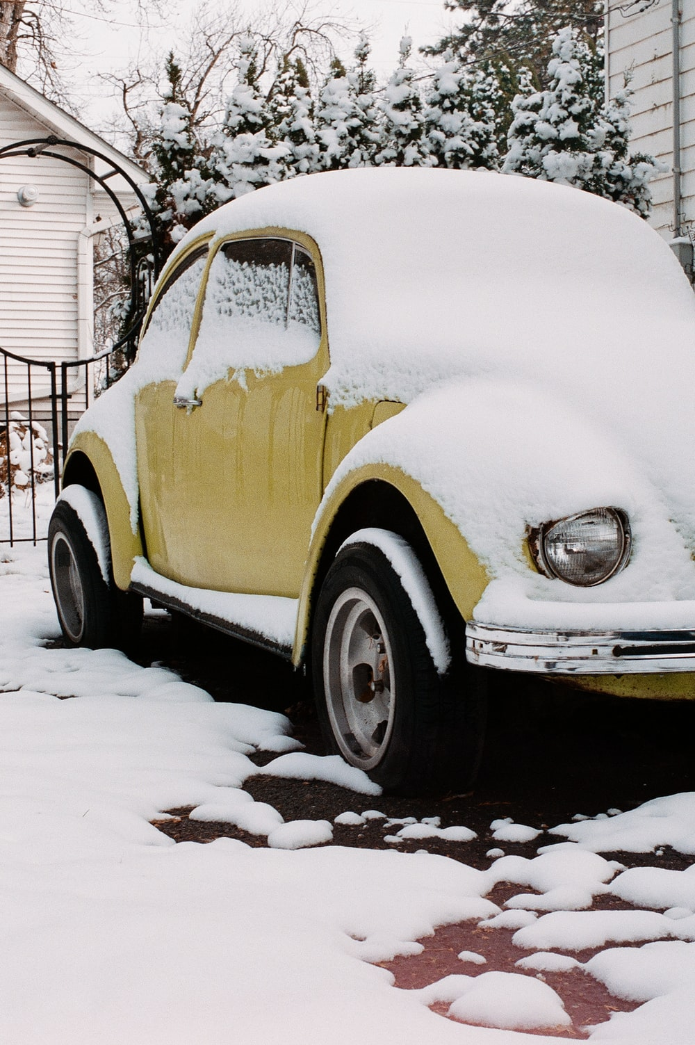 white and brown vintage car covered with snow