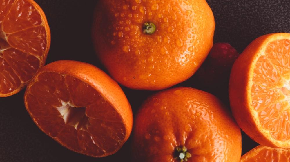 3 orange fruits on black background