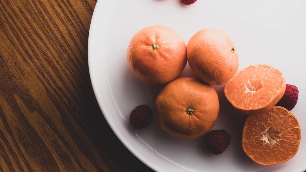three orange fruits on white ceramic plate