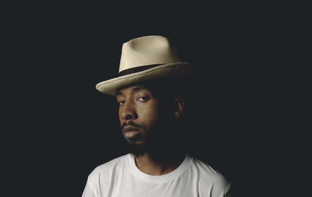 man in white crew neck shirt wearing brown fedora hat