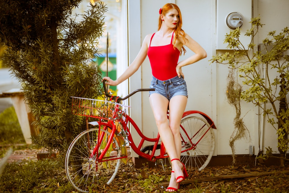 woman in red tank top and blue denim shorts standing beside red bicycle
