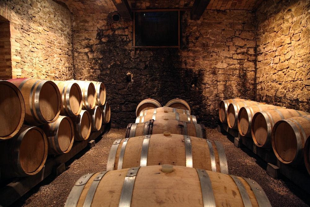 brown wooden barrels on brown brick wall