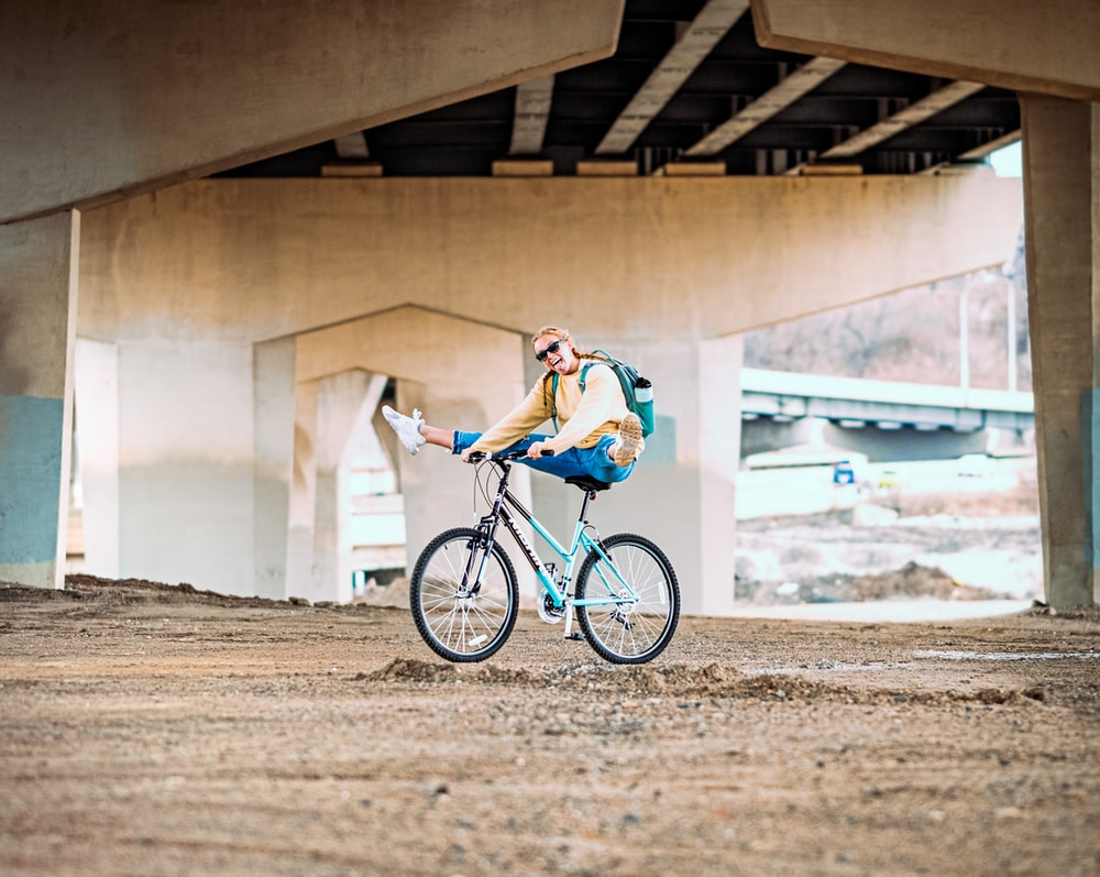 man in blue and white shirt riding on black bicycle during daytime