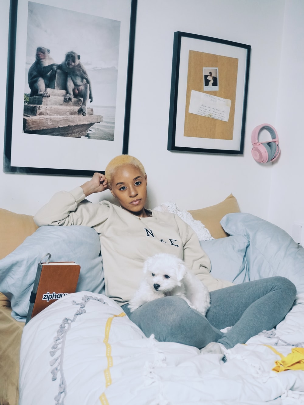 woman in gray long sleeve shirt lying on bed beside white dog