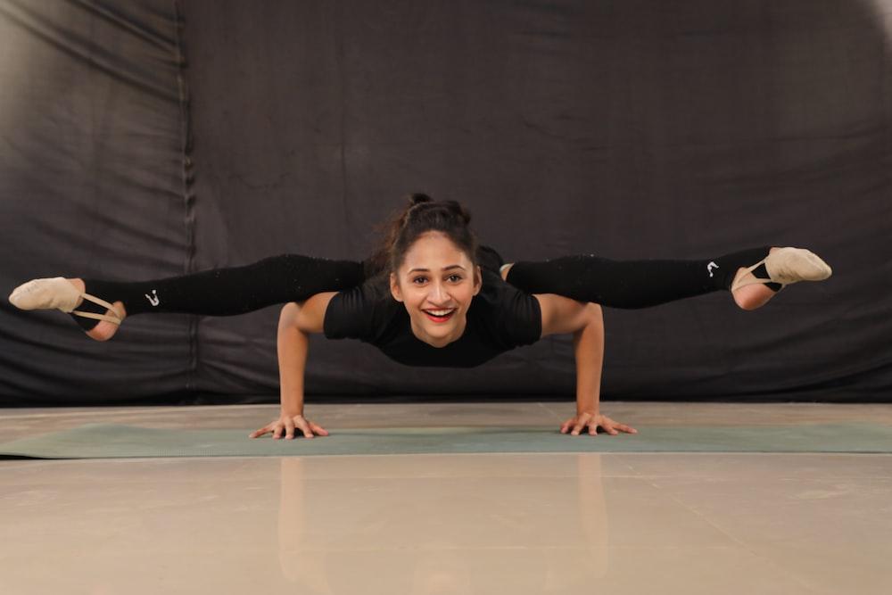 woman in black t-shirt and black pants doing yoga